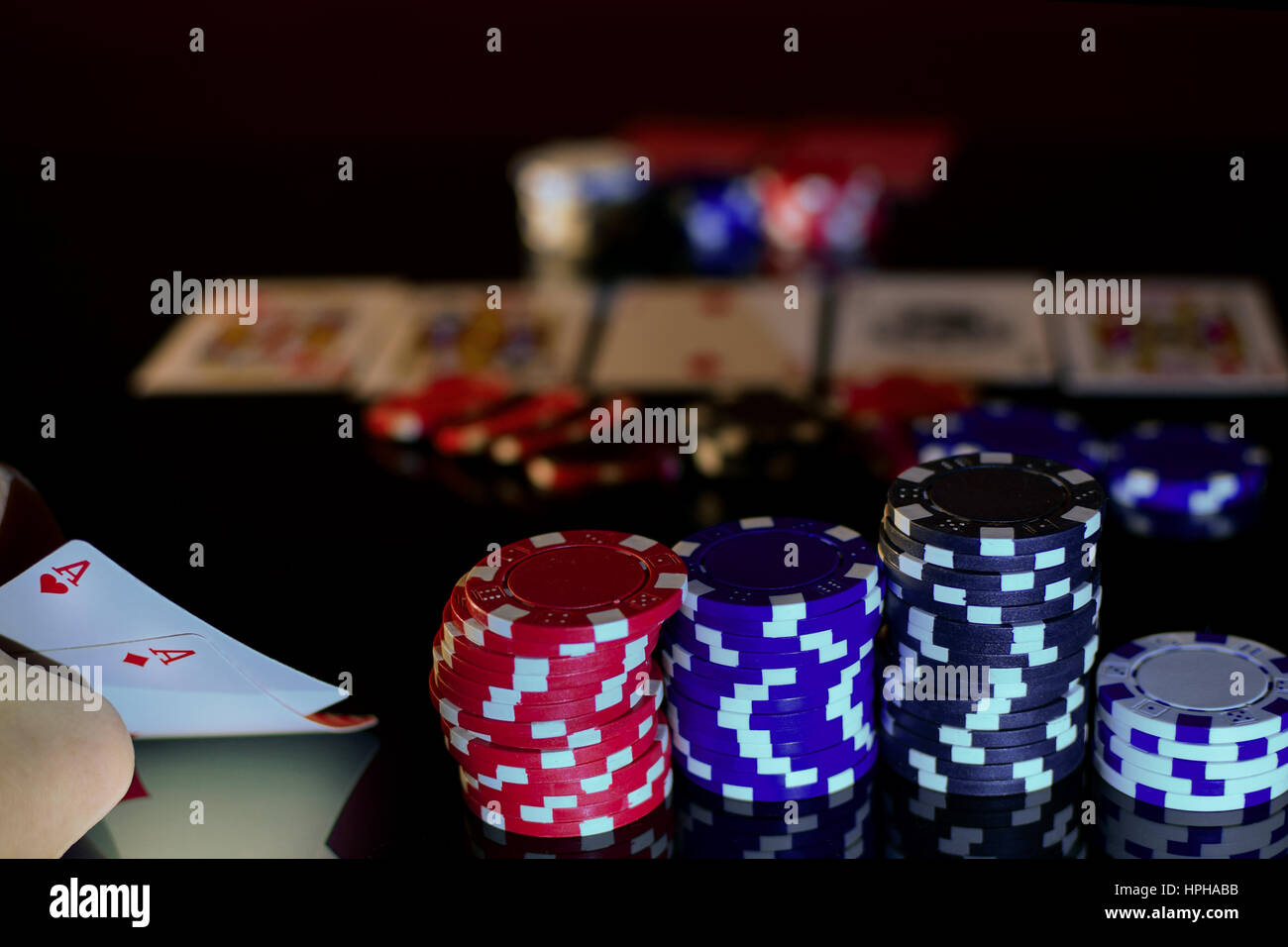 Pair of aces in pocket pair and poker chips. Black surface, horizontal view. - Stock Image