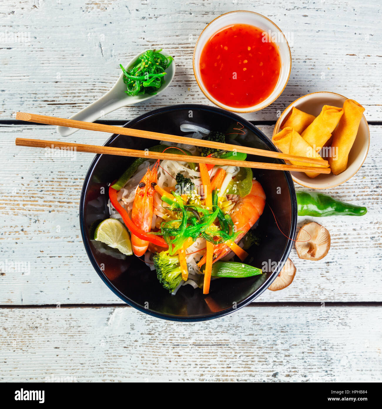 Asian prawns with rice noodles and spring rools, top view, served on old wooden planks. - Stock Image