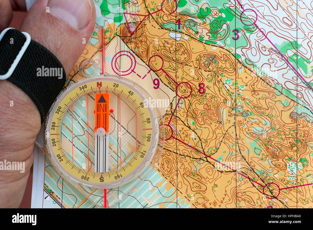 Hand holding a compass on an orienteering map - Stock Image