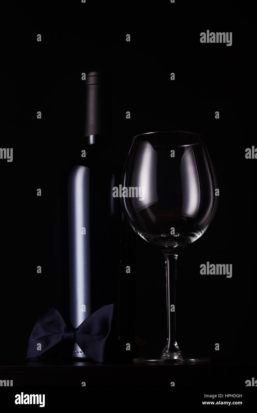 vertical front view of black red wine bottle with cap and no label, tall empty glass and a dark bow tie at the base - Stock Image