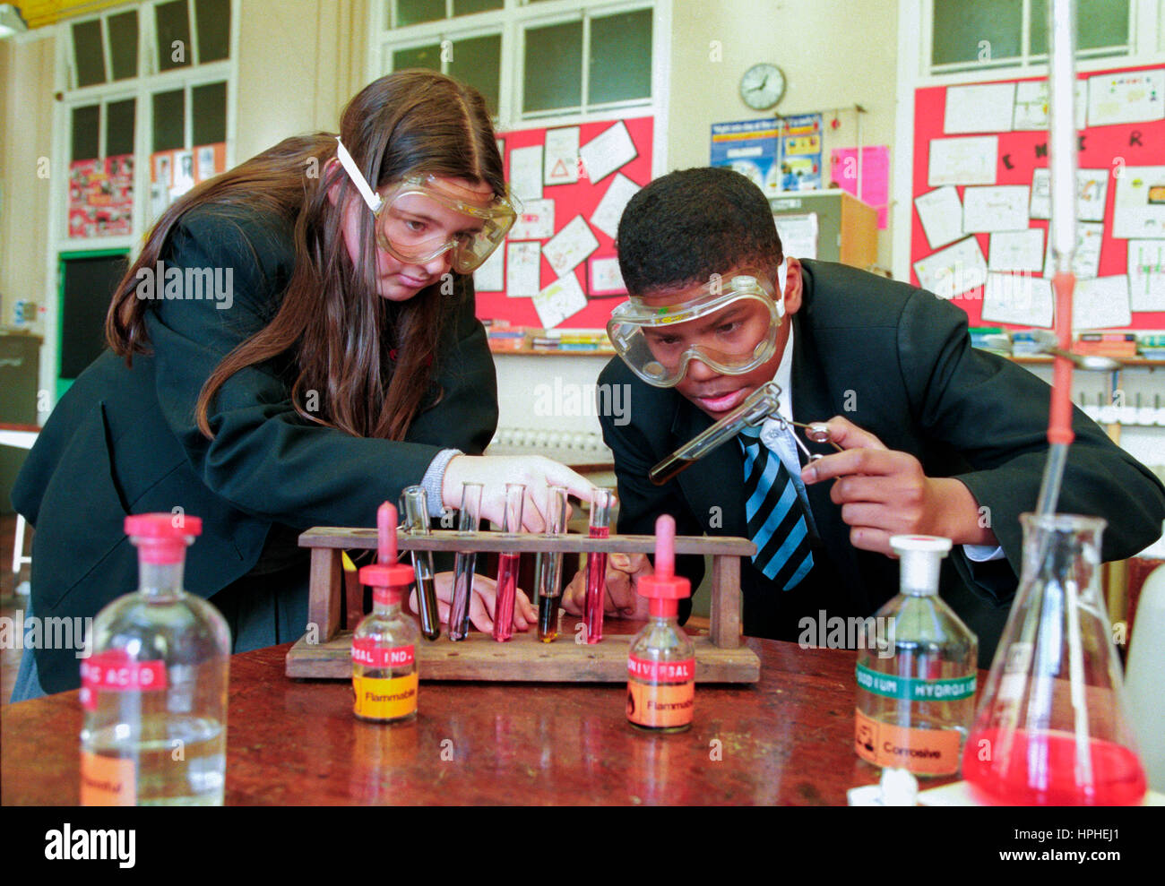 Secondary school pupils working on science experiments in classroom laboratories. - Stock Image