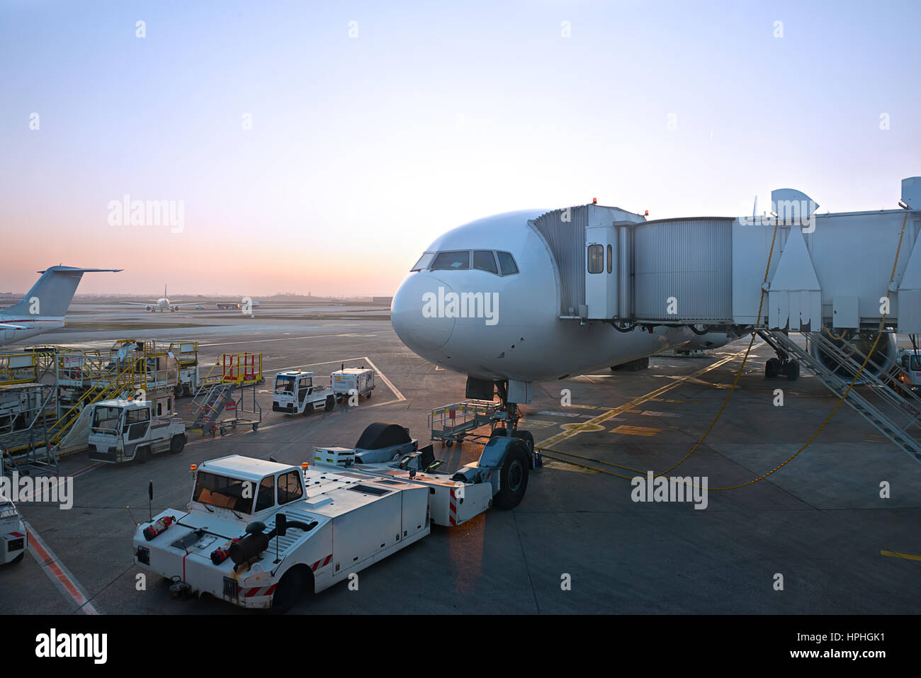 big jet plane preparing for pushback and departure in an airport evening lighting - Stock Image