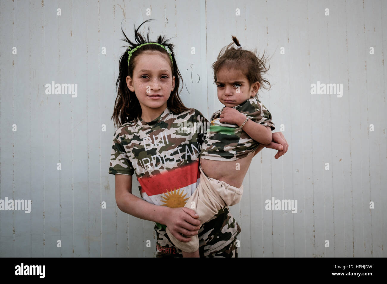 Refugee girl carrying her sickly baby sister wearing T shirts with the slogan BIJI KURDISTAN (Long Live Kurdistan) - Stock Image