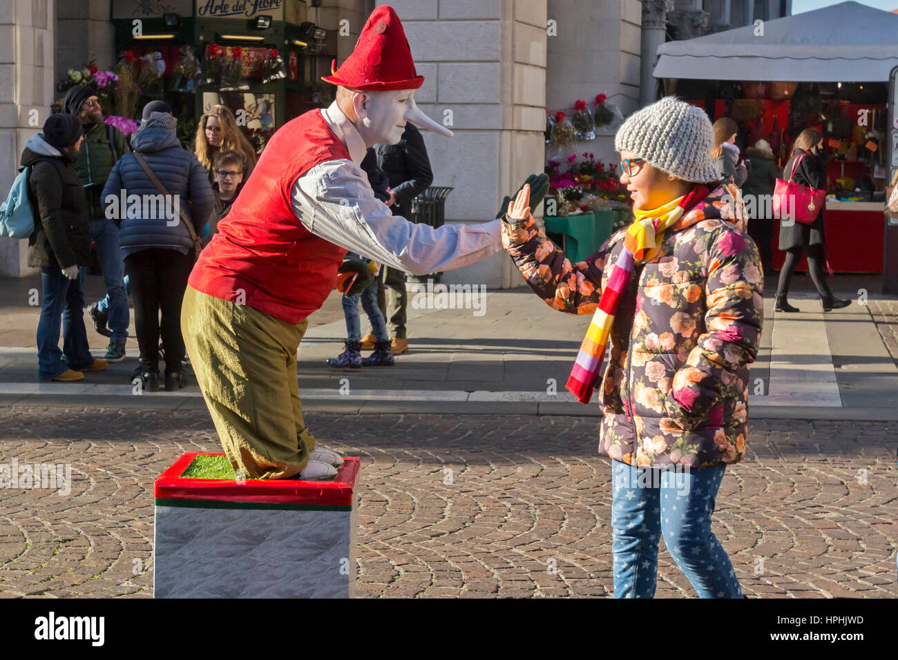A street clown entertains a young lady. - Stock Image