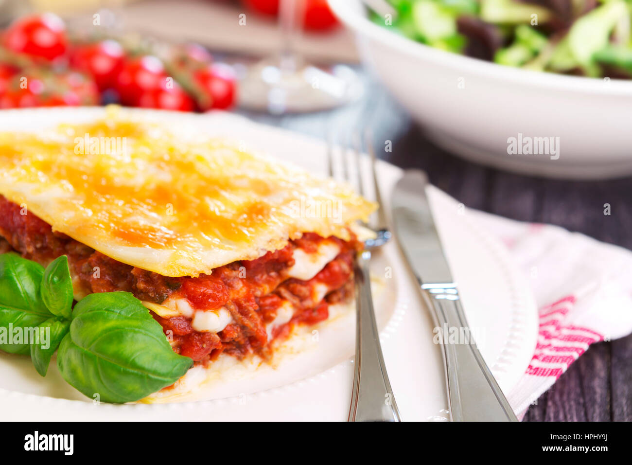 A portion of homemade lasagna on a plate, served with a salad on the side. - Stock Image