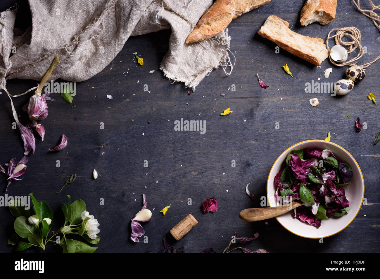 Healthy purple salad mix with fresh french bread over dark rustic wooden table, from above. Background layout with - Stock Image