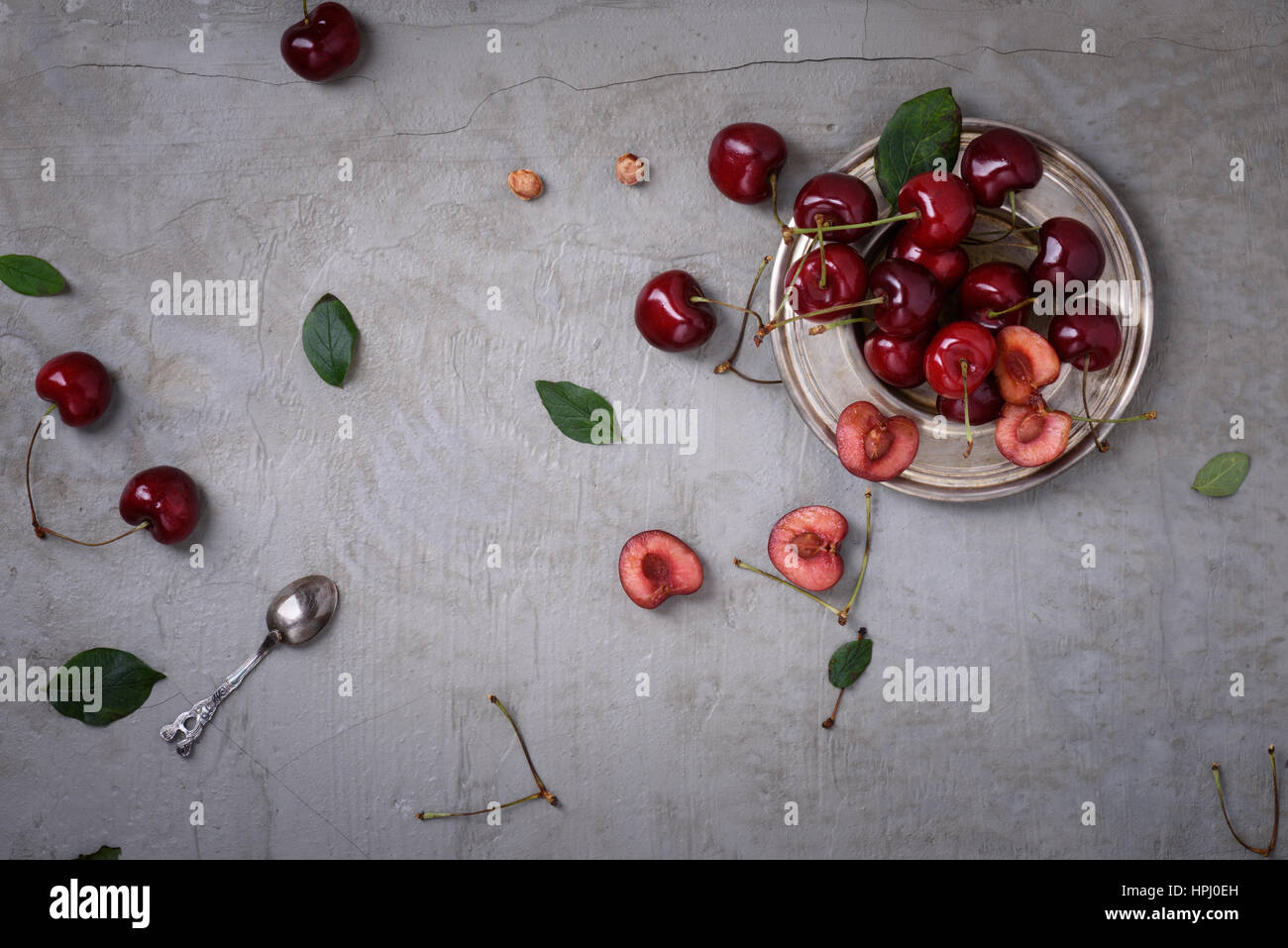 Cherry on a plate over grey rustic background, copy space, overhead view. Fresh berries, fruit. - Stock Image