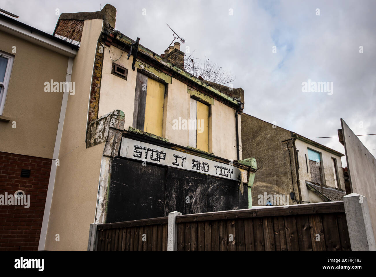 Stop it and tidy up. Boarded up empty property daubed with the slogan 'Stop it and tidy up' with a syringe - Stock Image