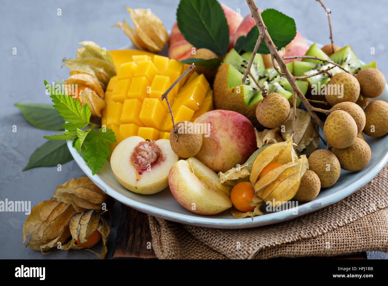 Tropical fruit plate with mango, apricots, longan and kiwi - Stock Image