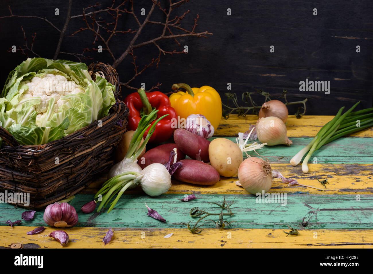 Organic seasonal vegetable ingredients over colorful wooden table. Healthy food or vegetarian diet concept. Stock Photo