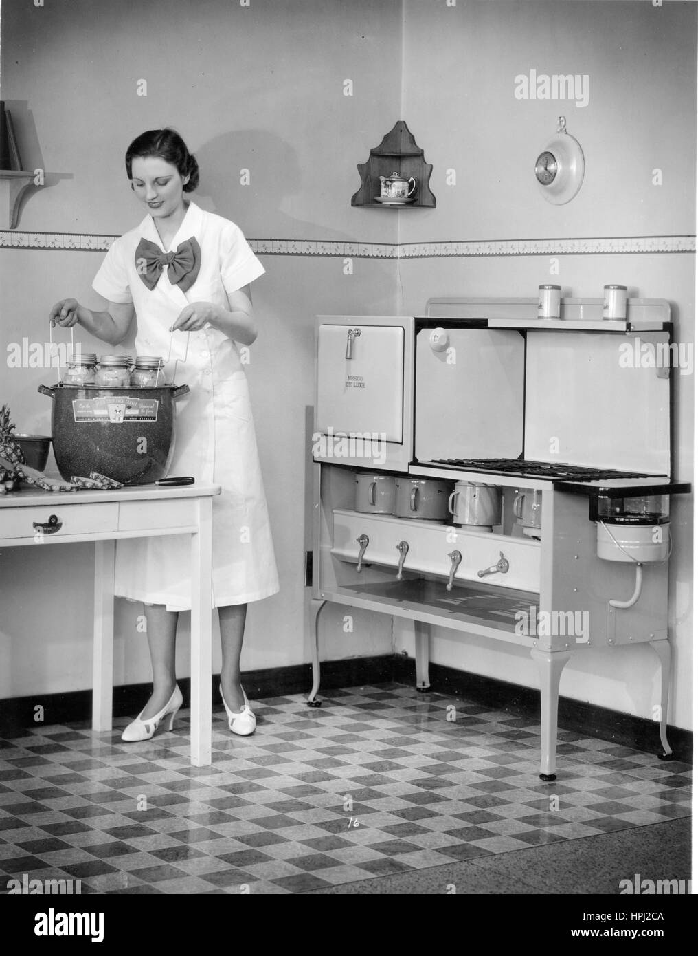prim homemaker in front of a nesco de luxe oil cook stove in a - 1920s Kitchen