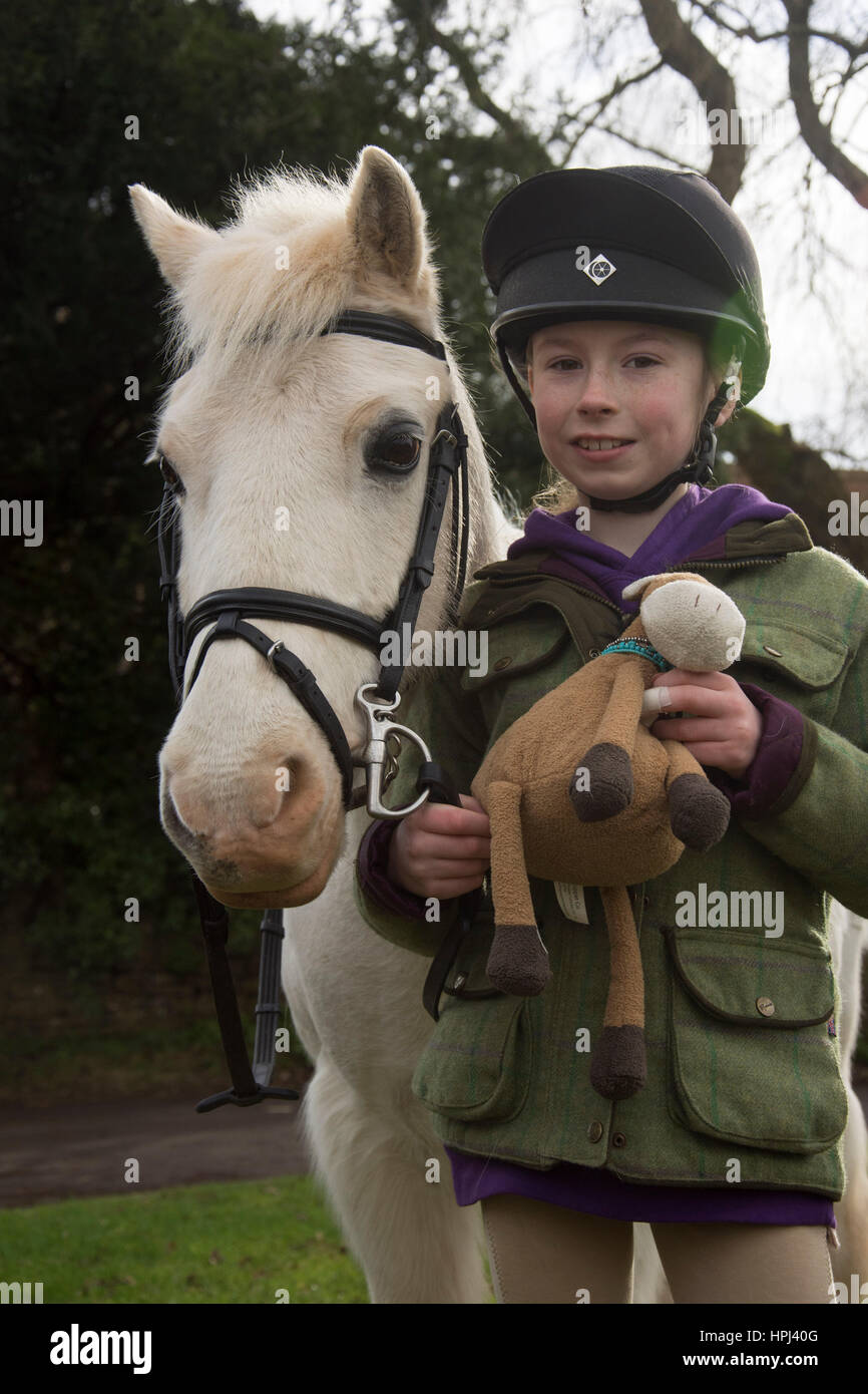 England, United Kingdom. February 16 2017.   Ella Newman aged 10, is pictured with her pony Blue, aged 27 in the - Stock Image