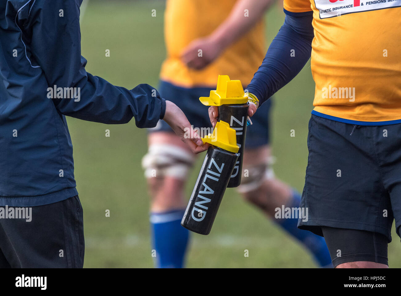 Rugby union player is handed liquids in a plastic bottle. - Stock Image