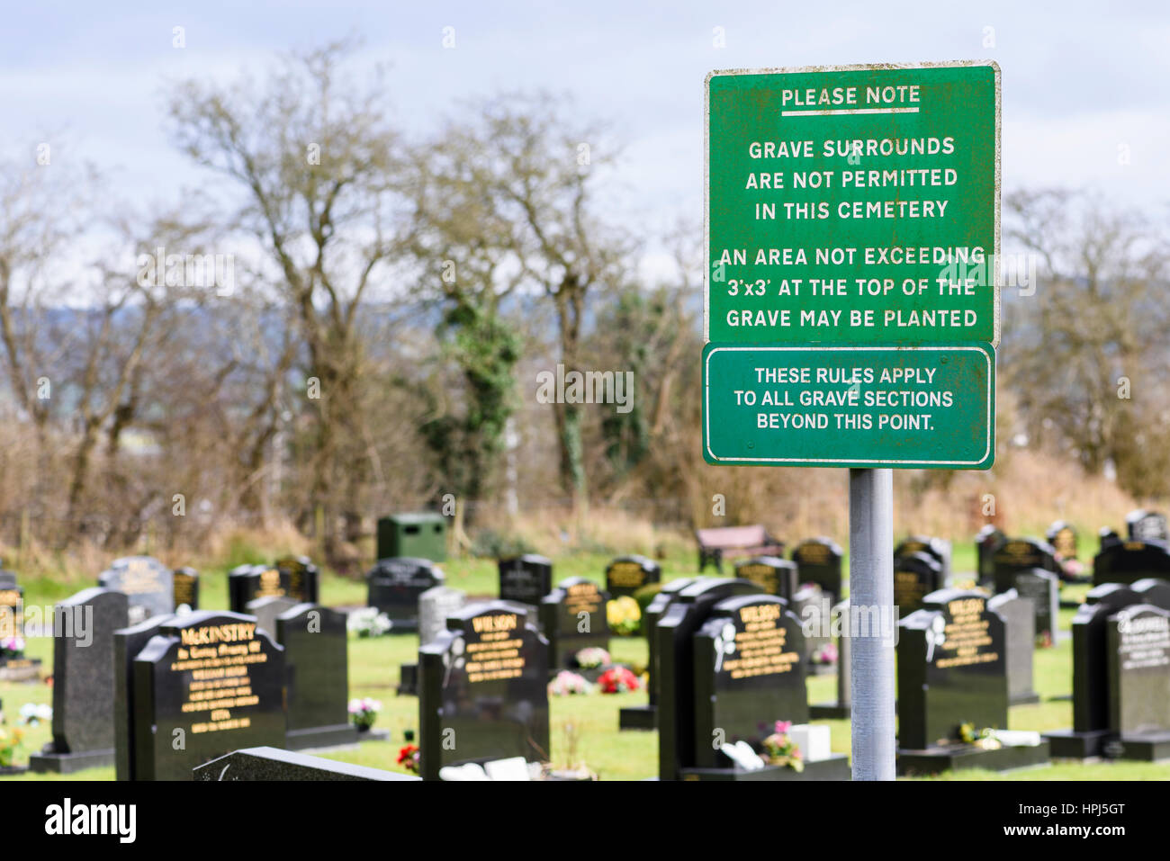 Sign in a lawn cemetery reminding people that grave surrounds are not permitted. Stock Photo