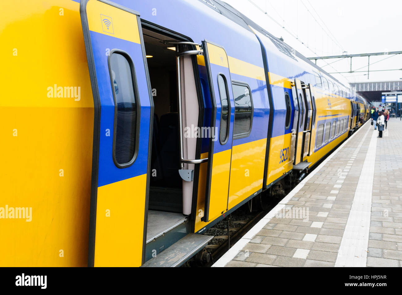 Nederlandse Spoorwegen yellow and blue train at a platform in the Netherlands - Stock Image