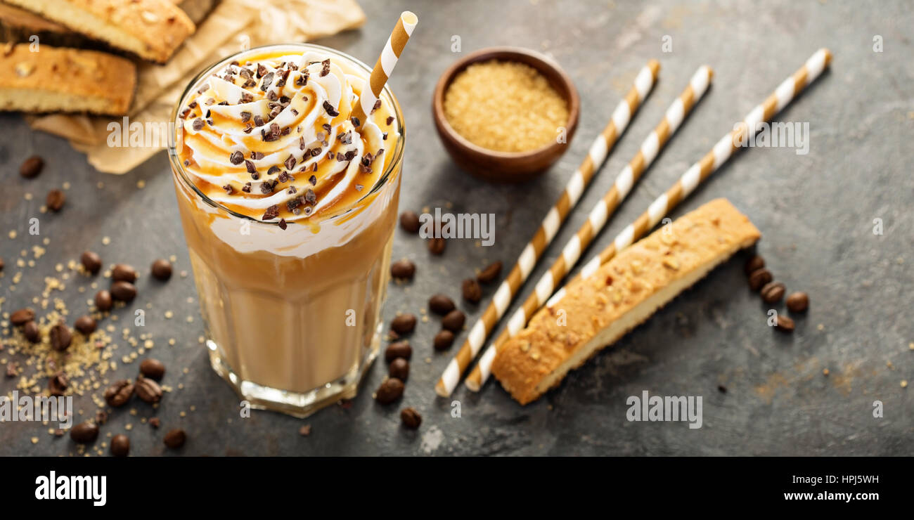 Iced caramel latte coffee in a tall glass with syrup and whipped cream - Stock Image