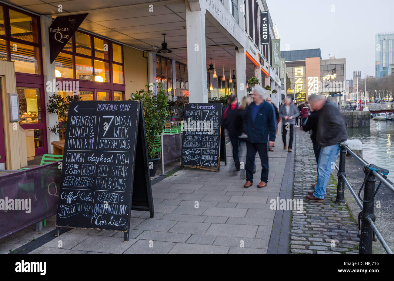 Menu boards outside a restaurant in the harbour area of Bristol are designed to entice customers in. - Stock Image