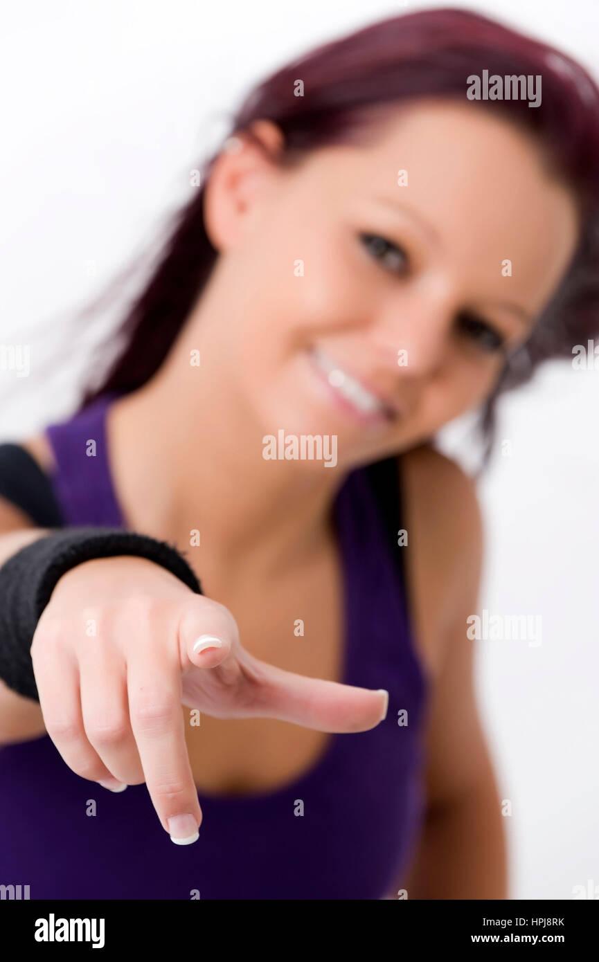 Model released , Sportliche, junge Frau zeigt mit Zeigefinger - sporty woman - Stock Image