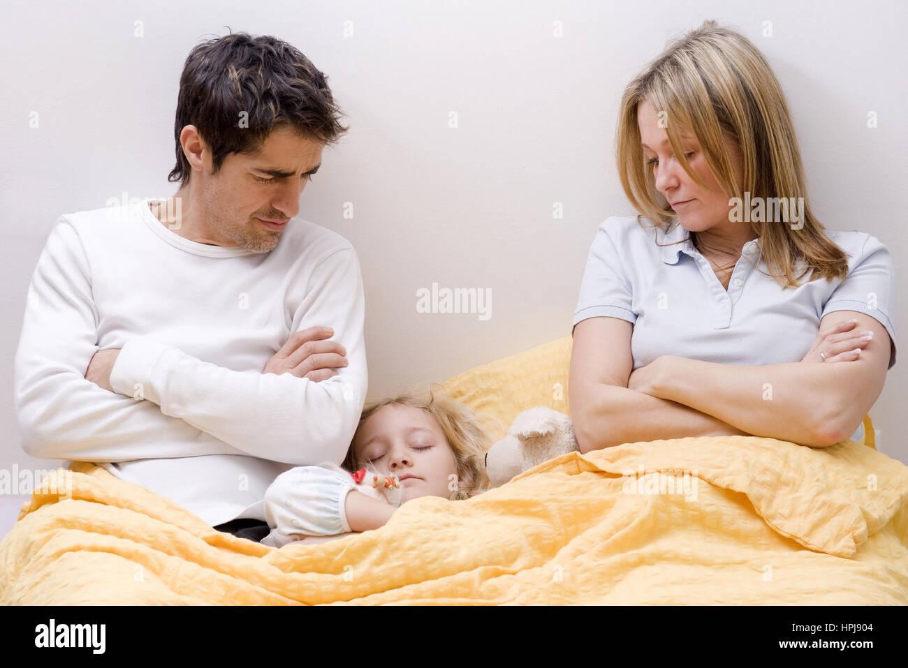 Model released , Tochter schlaeft zwischen den Eltern im Ehebett - daughter sleeping between parents in bed Stock Photo