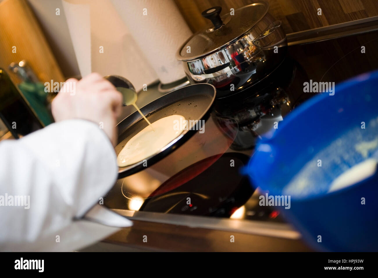 Crepes in der Pfanne zubereiten - cooking crepes - Stock Image