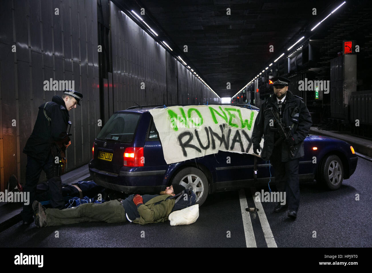 Police attending three climate activists who have blocked the inbound tunnel to Heathrow Airport in protest againts - Stock Image