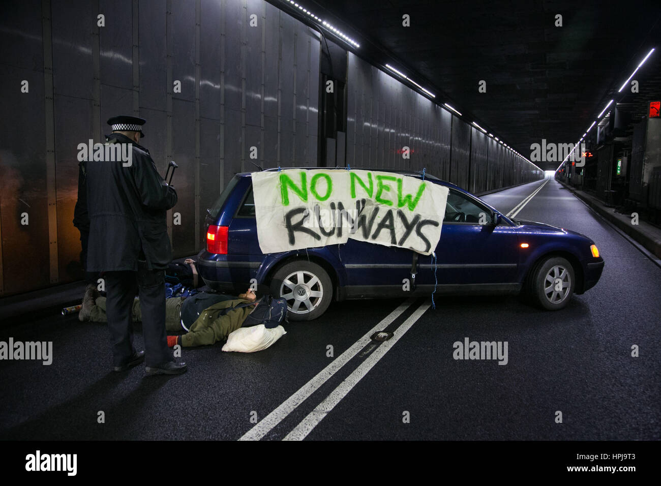 Three Rising Up! activists have blockaded the main access road into Heathrow Terminals 1, 2 and 3, by chaining themselves - Stock Image
