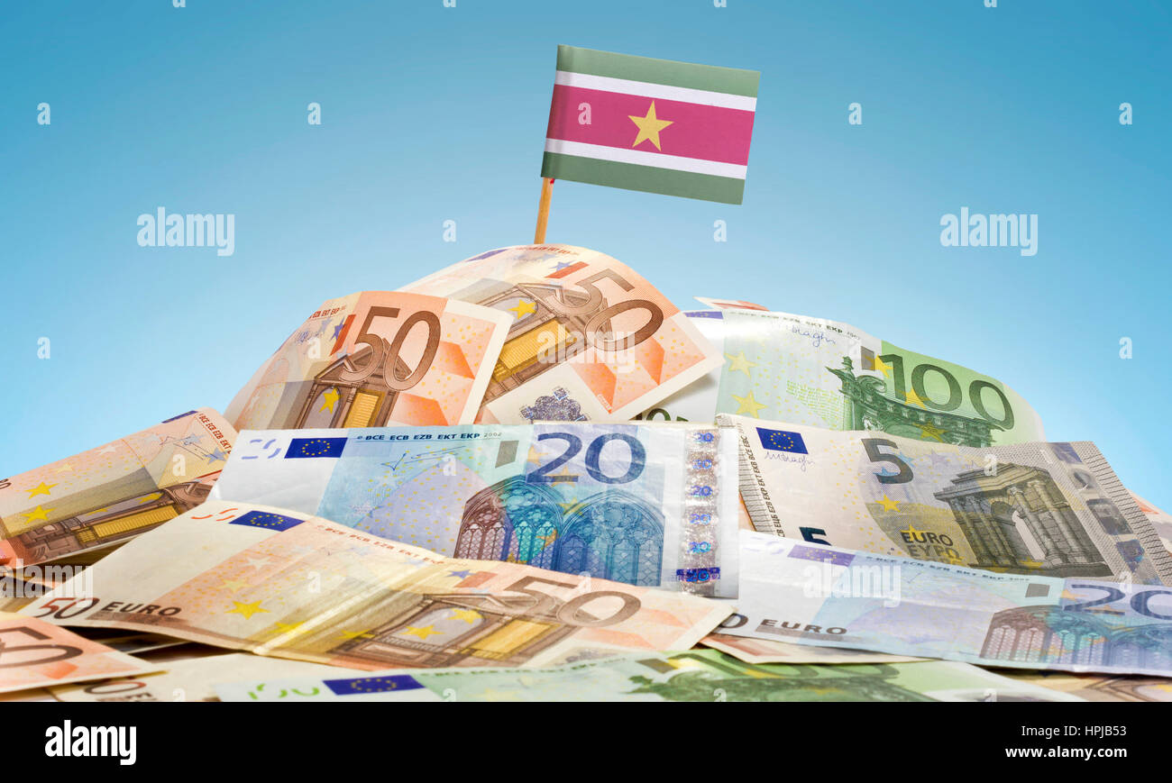 The national flag of Suriname sticking in a pile of mixed european banknotes.(series) - Stock Image