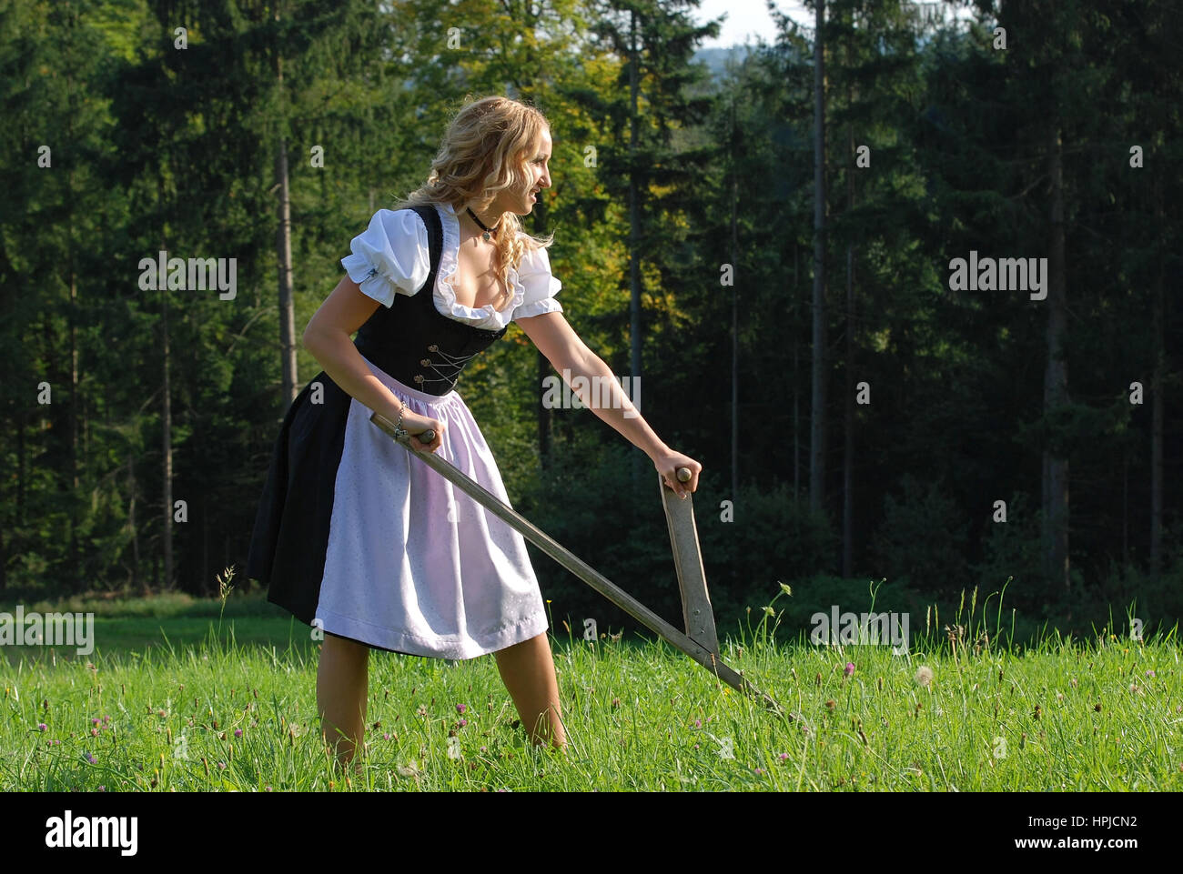 Model released , Junge Baeurin im Dirndl mit Sense - young woman in dirndl with scythe Stock Photo