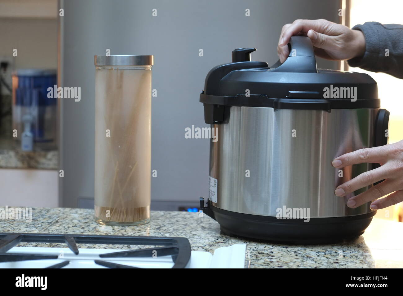 A pair of hands opening a pressure cooker - Stock Image