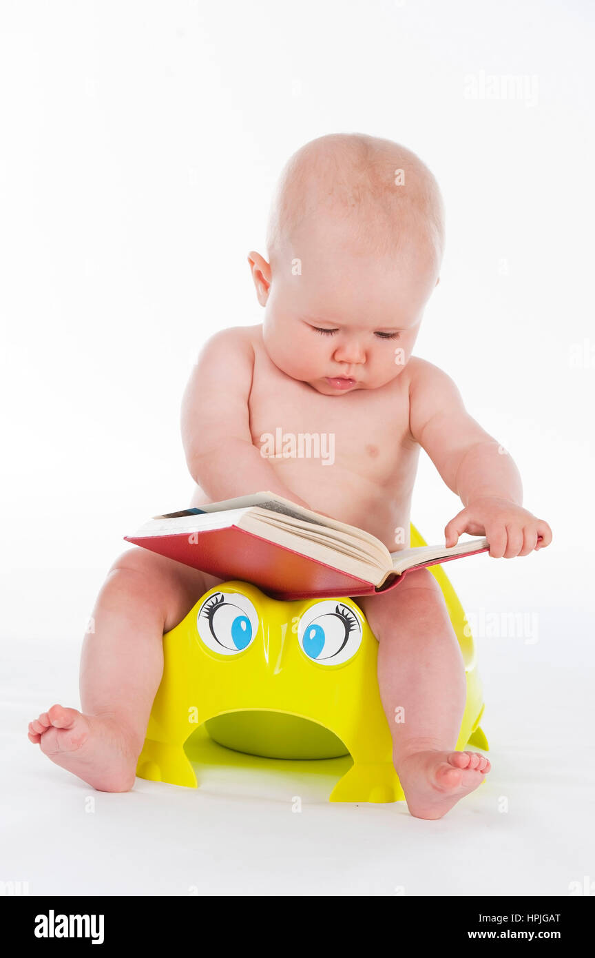 Model released , Baby, 10 Monate, sitzt mit Buch am Toepfchen - little child sitting on potty Stock Photo