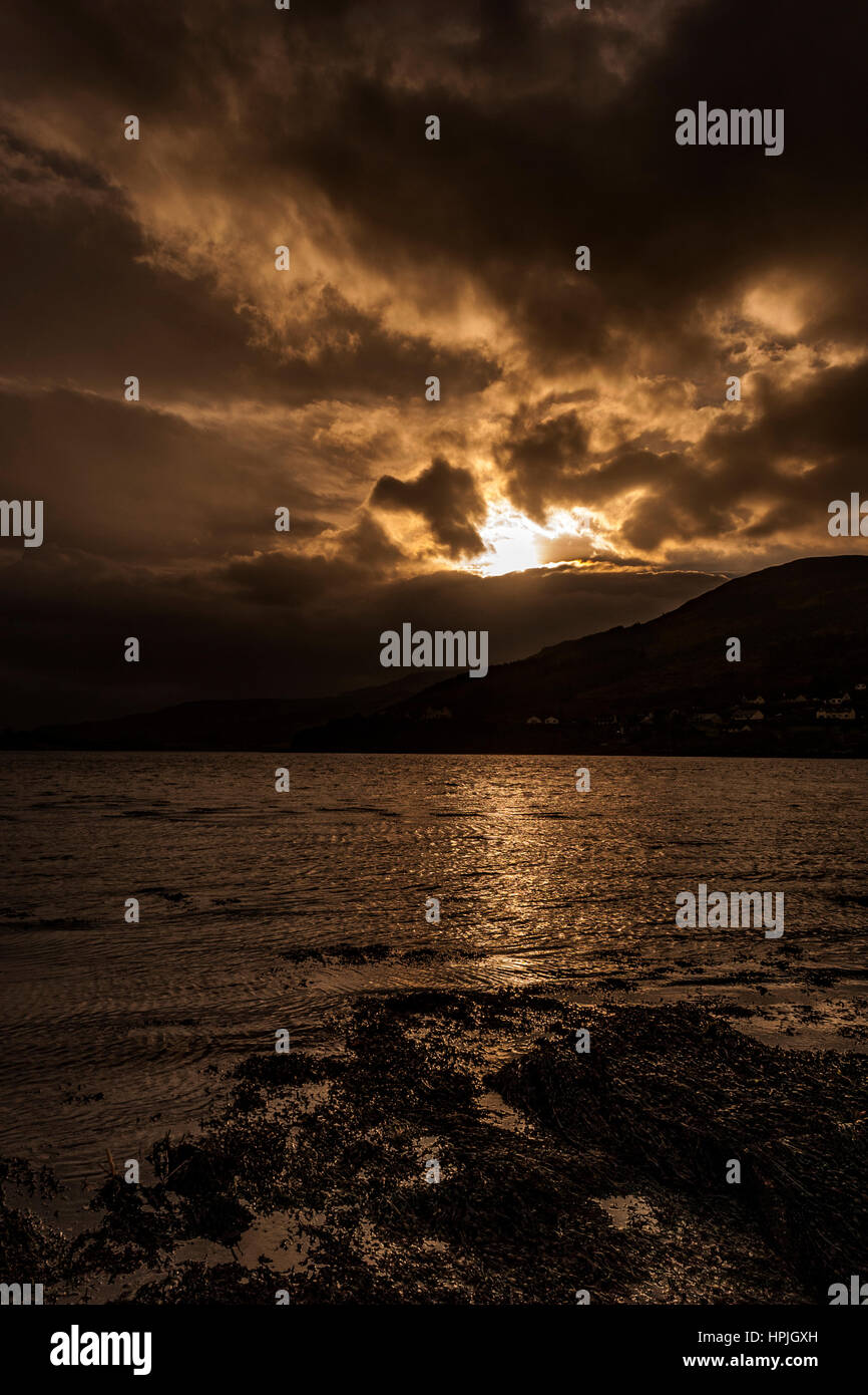 Winter afternoon sun across Loch Portree, looking toward Viewfield Road and the Black Cuillin mountains Stock Photo
