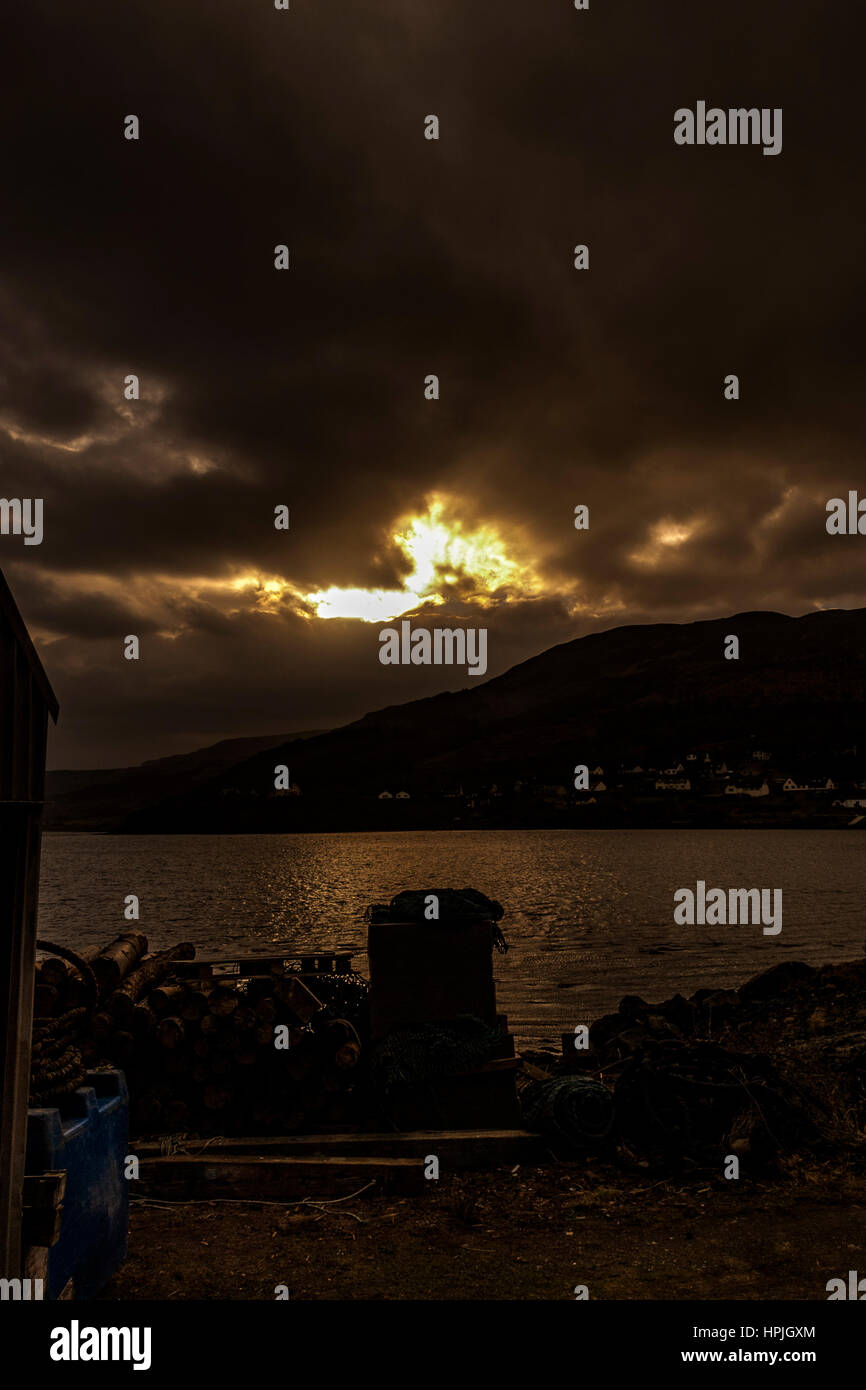 Winter afternoon sun across Loch Portree, looking toward Viewfield Road and the Black Cuillin mountains - Stock Image