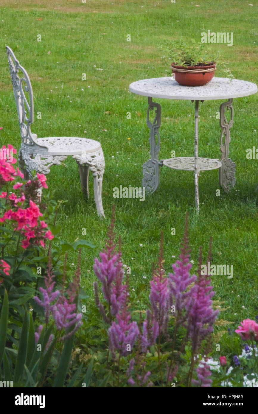 White painted cast iron garden chair and table on green ...