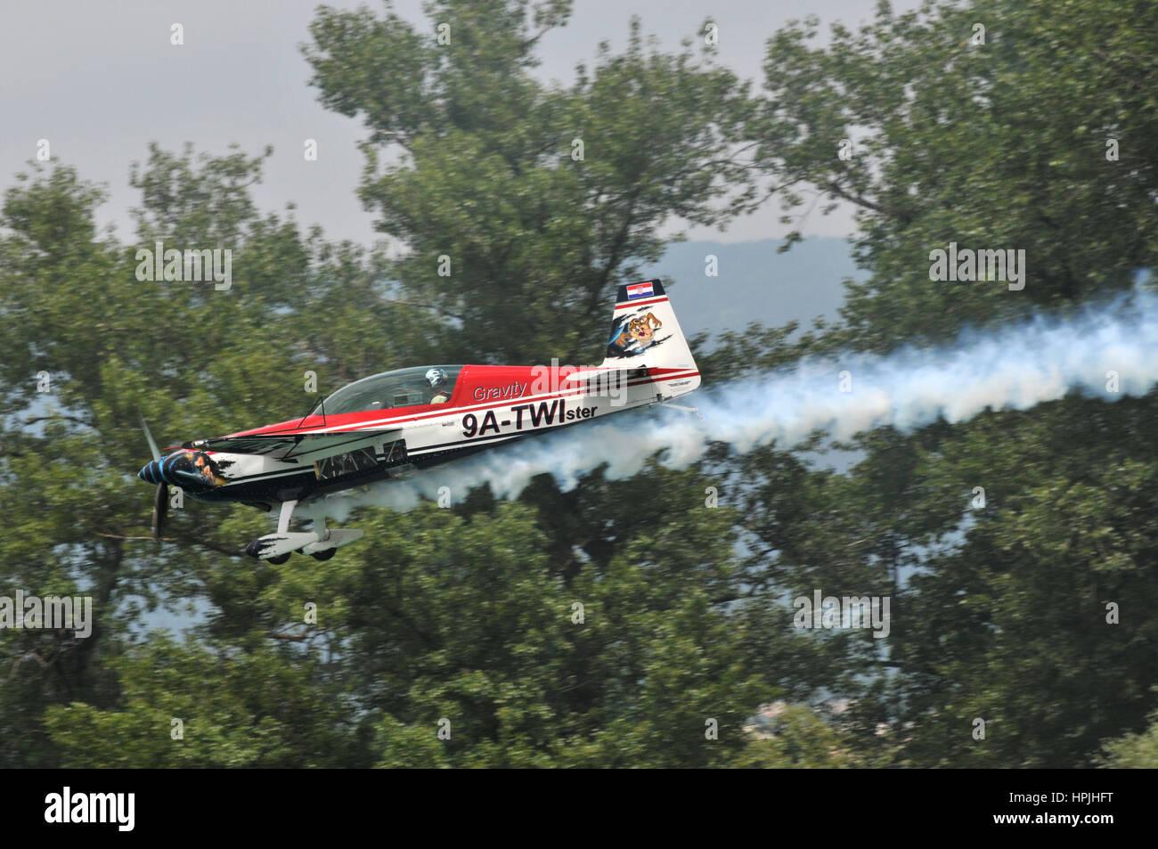 Croatian pilot Branimir Ambrekovic in his Extra 300 'Twister' aerobatic plane performs stunt trailing white - Stock Image
