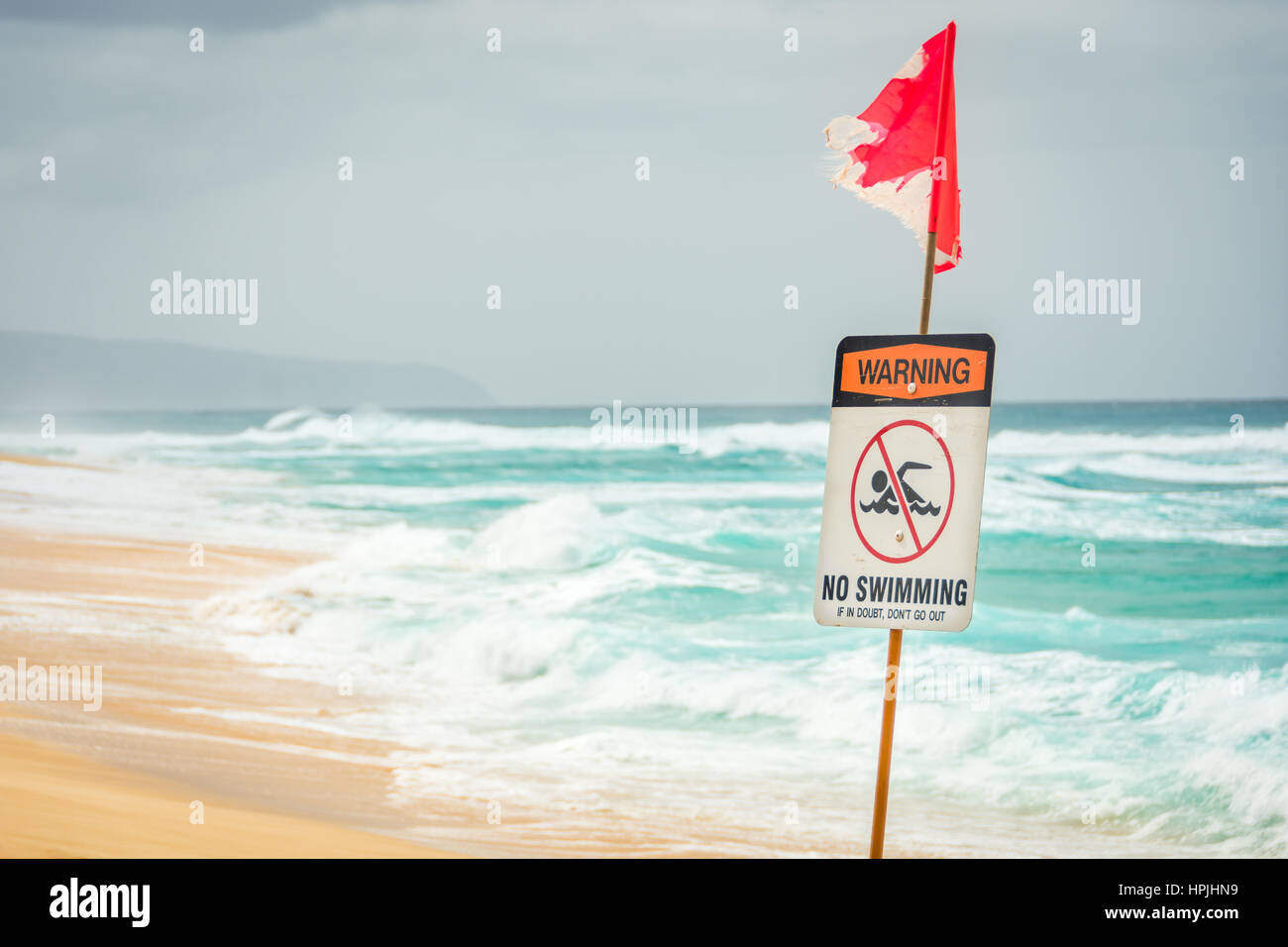 A warning sign indicating no swimming due to large, dangerous ocean waves. Stock Photo