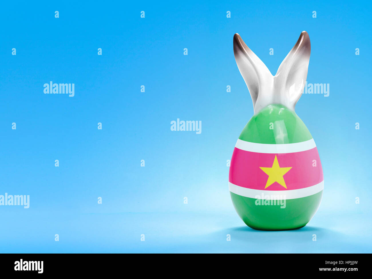 Colorful cute ceramic easter egg with rabbit ears and the flag of Suriname .(series) - Stock Image