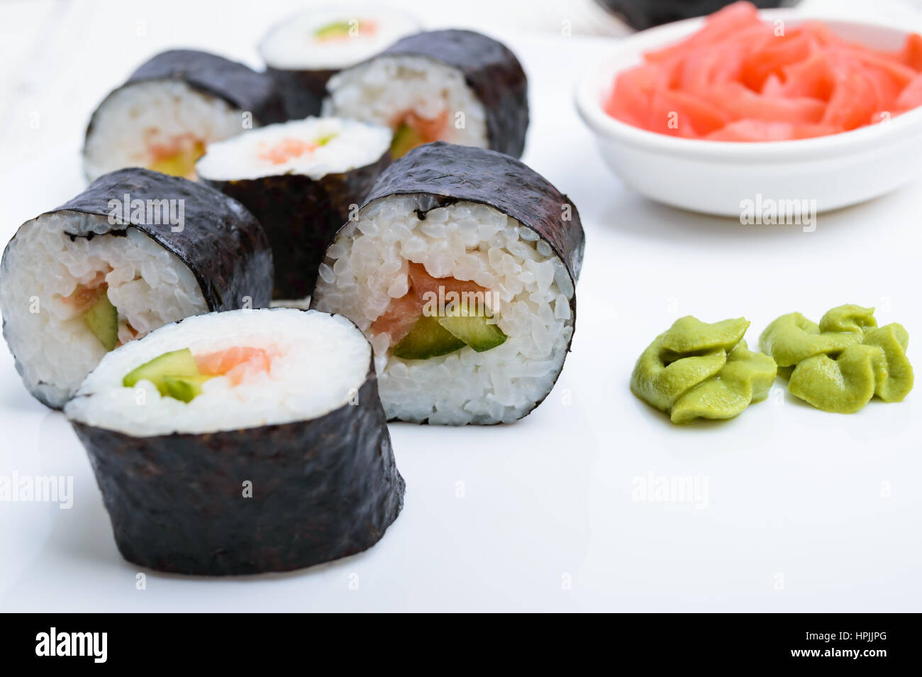 Traditional eastern dish with salmon sushi rolls on a white plate. Close-up. - Stock Image