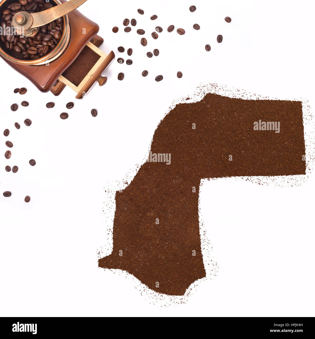 Coffee powder in the shape of Western Sahara and a decorative coffee mill.(series) - Stock Image