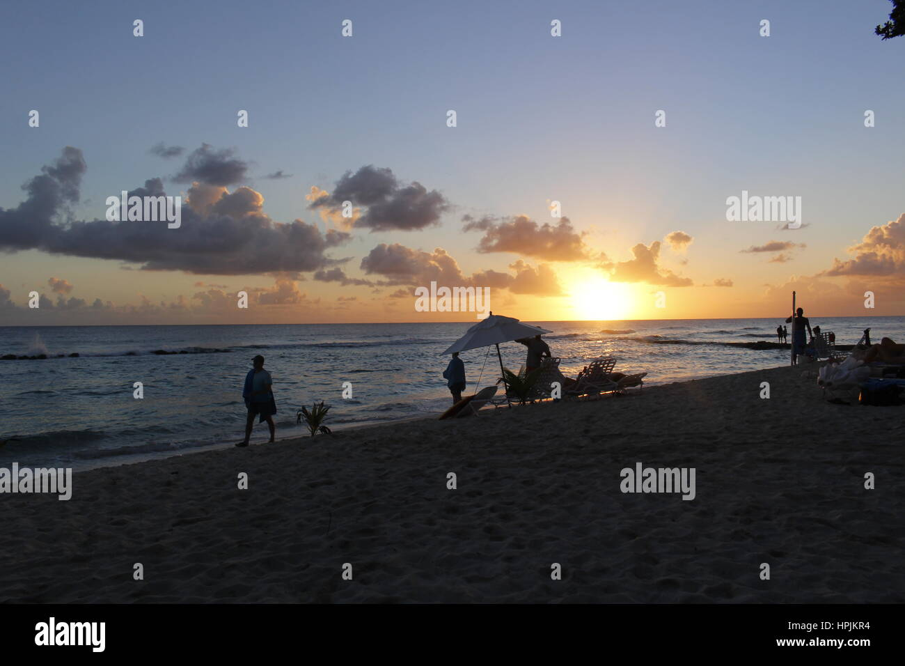 Silhouettes of people on the beach at sunset, Hasting, Barbados, Caribbean. - Stock Image
