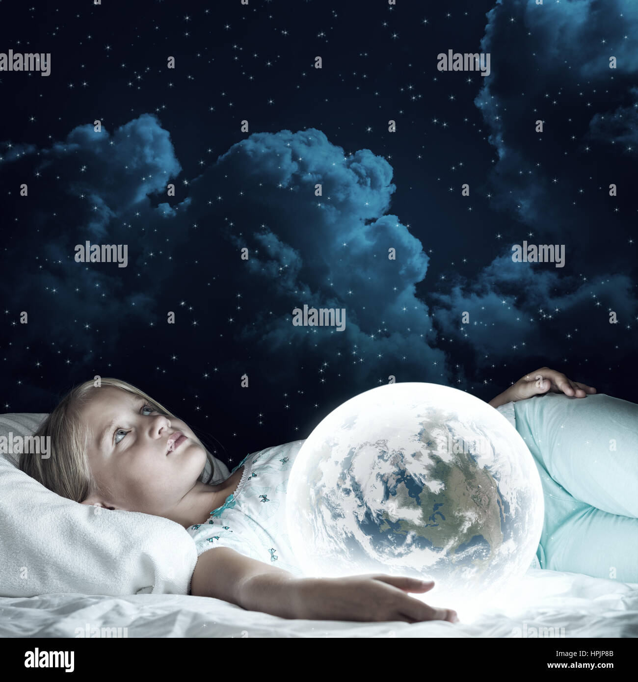 Girl in her bed and glowing globe - Stock Image