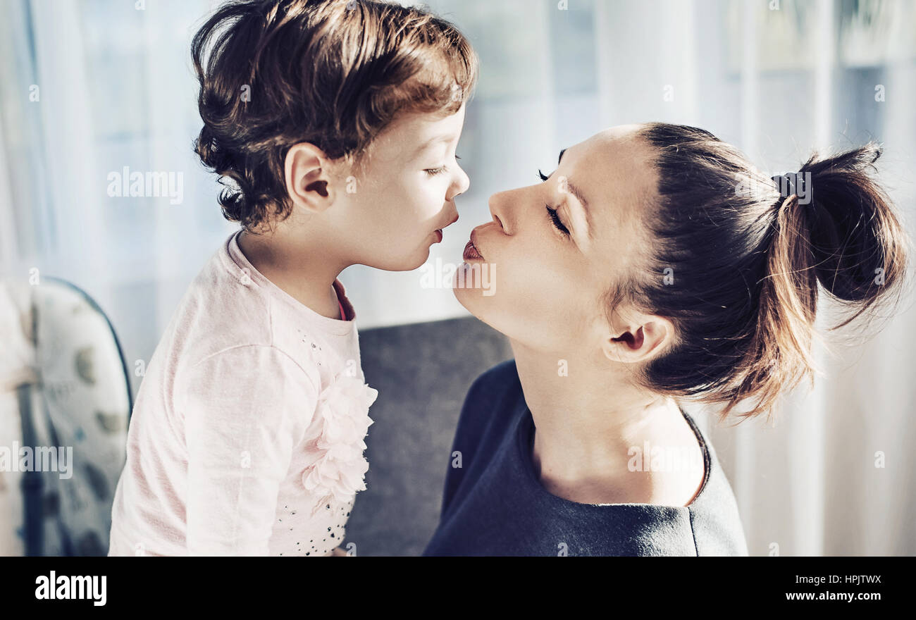 Portrait of a mother kissing her beloved daughter - Stock Image