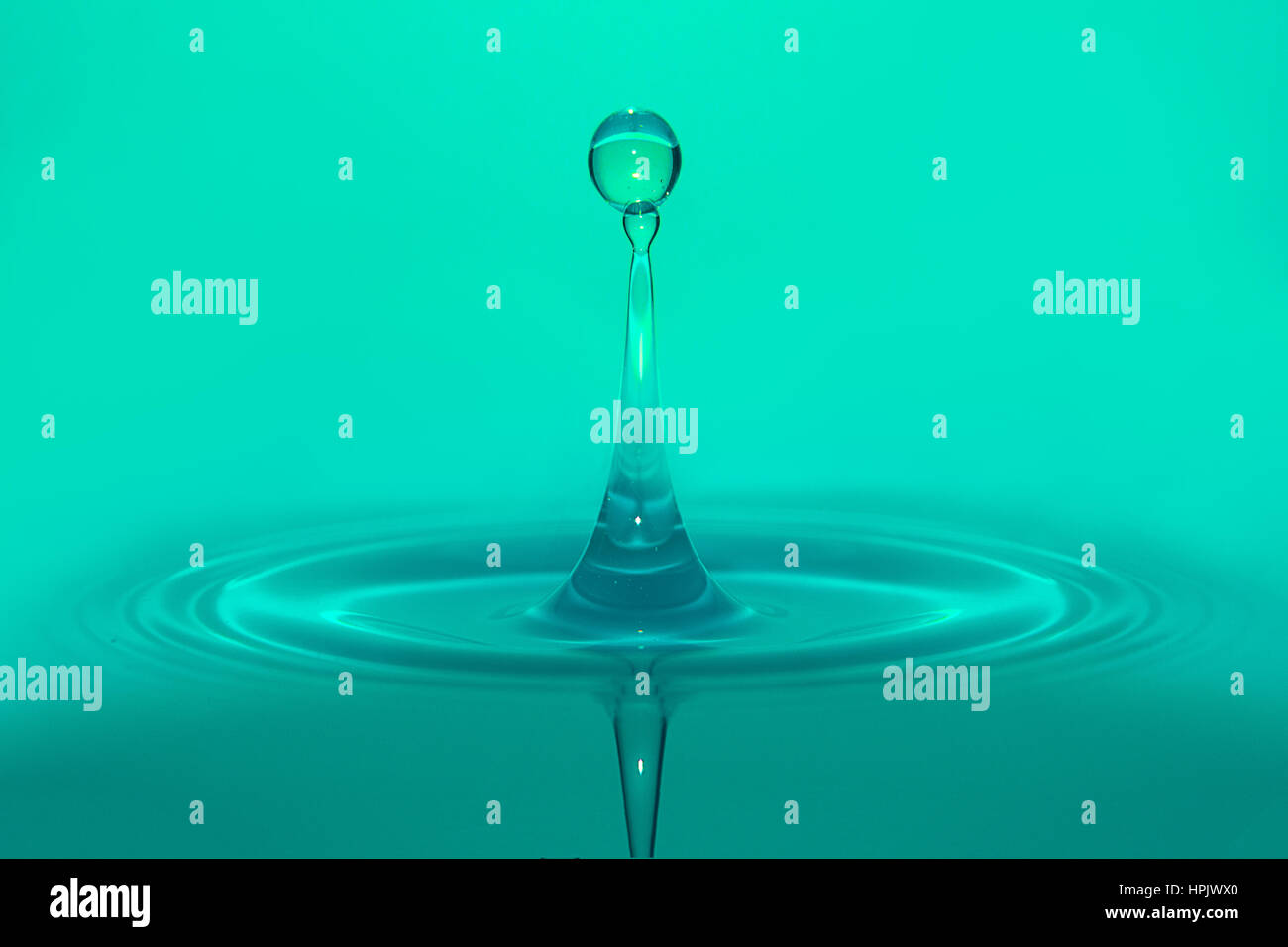 Water droplets splashing cyan background, great for spa use - Stock Image