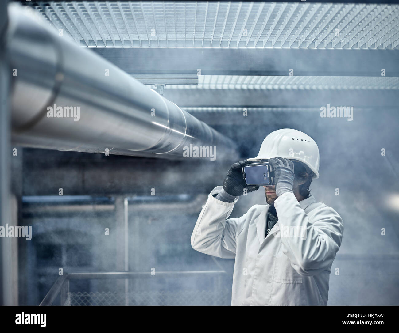 Man with VR goggles, white helmet and lab coat standing in front of industrial plant, Austria - Stock Image