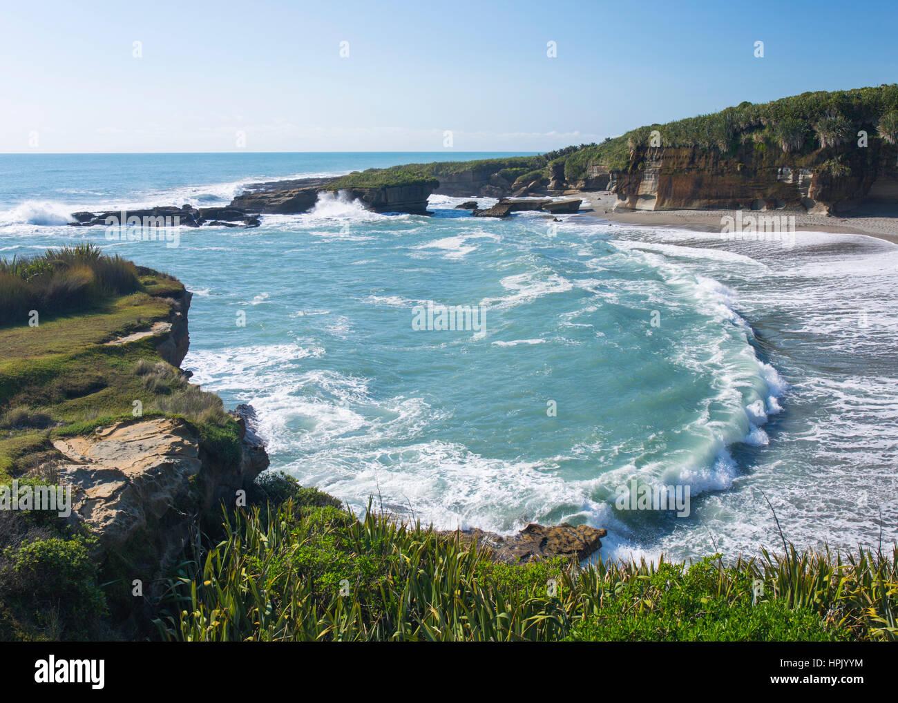 Punakaiki, Paparoa National Park, West Coast, New Zealand. Waves from the Tasman Sea pounding secluded beach at - Stock Image