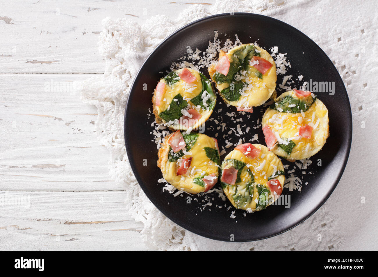 Tasty breakfast: frittata with spinach, ham and cheese on a plate close-up on the table. horizontal view from above - Stock Image