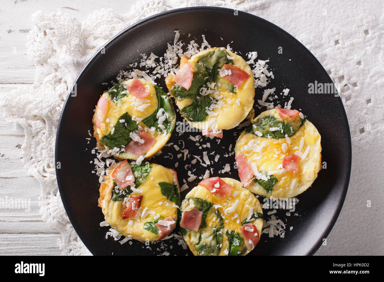 frittata with spinach, ham and cheese on a plate close-up on the table. horizontal view from above - Stock Image