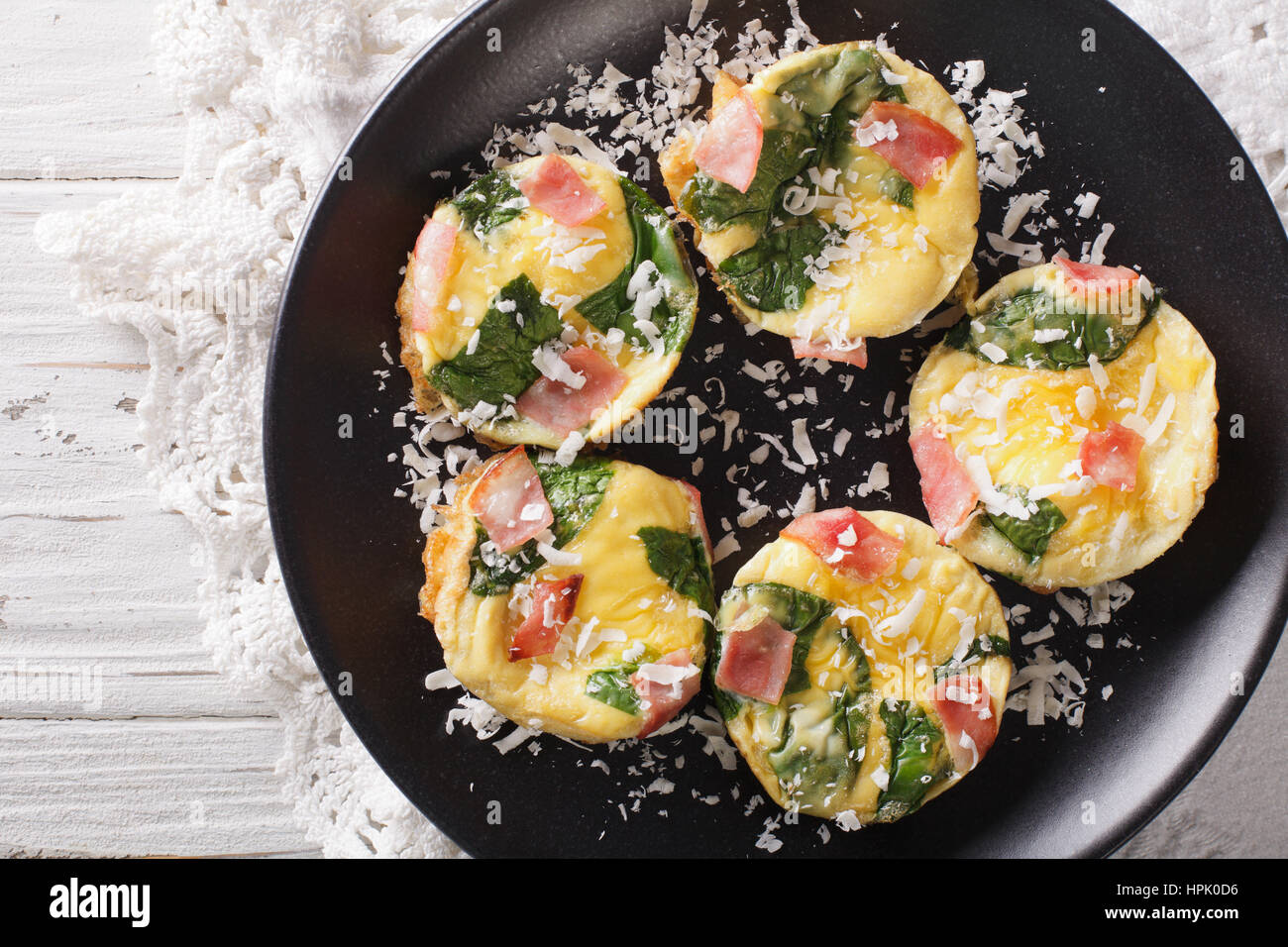 Omelet with spinach, ham and cheese on a plate close-up on the table. Horizontal view from above - Stock Image