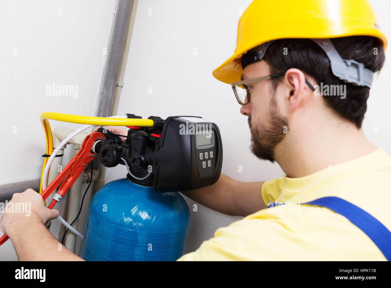 plumber installing new water filtration system - Stock Image