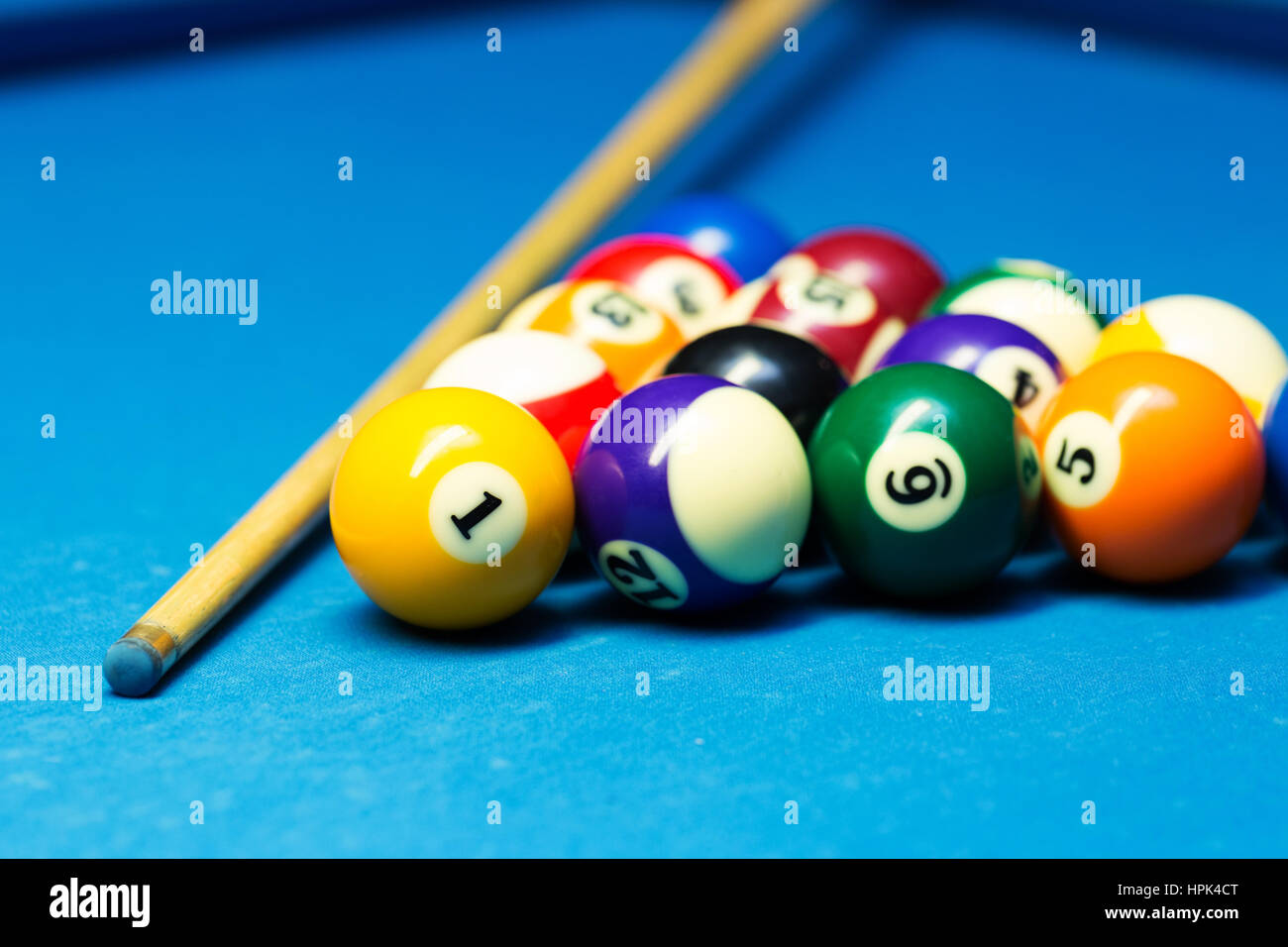 pool billiard balls and cue on the blue cloth table - Stock Image