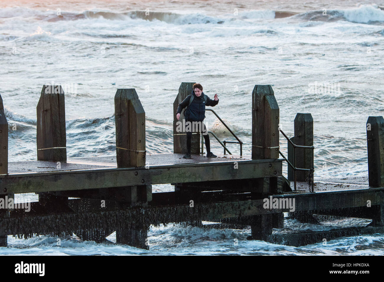 Aberystwyth Wales UK, Thursday 23 Feb 2017 UK Weather: Teenagers on the jetty in Aberystwyth playing a risky game - Stock Image